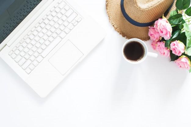 plano-puesta-ordenador-portatil-sombrero-casual-taza-cafe-rosas-rosas-vista-superior-sobre-fondo-blanco-espacio-copia_1428-221